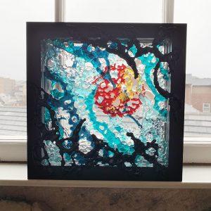 Framed glass artwork commission on window ledge